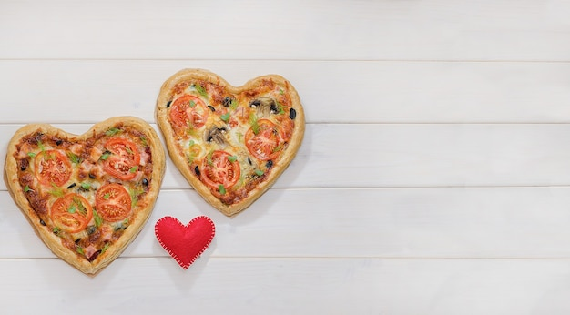 Two heart-shaped pizzas on a white wooden table with copy space with a red heart. valentine's day, love.