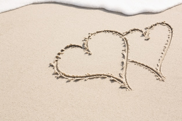 Two heart shapes drawn on sand