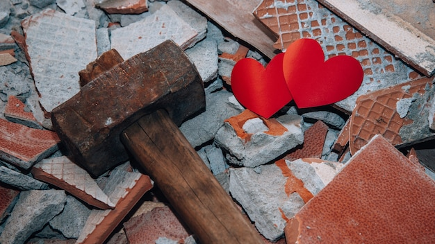 Two hearts among shards next to hammer concept of broken love unhappy relationships difficult period