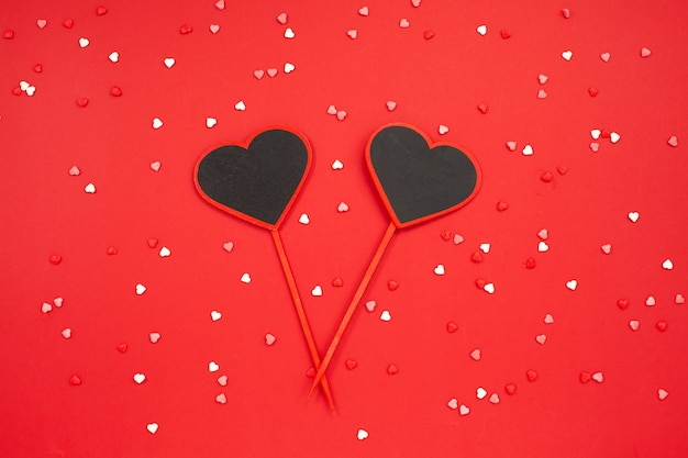Two hearts blackboard shaped over red festive background
