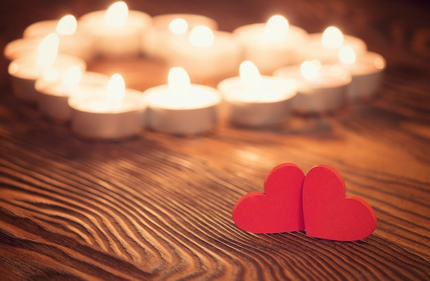 Two hearts, burning candles on wooden. valentine's day