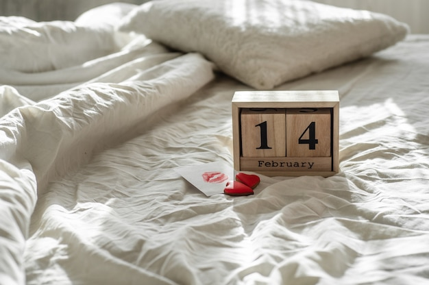 Two hearts cookies, a note with a kiss with wooden calendar 14 february on a white bed