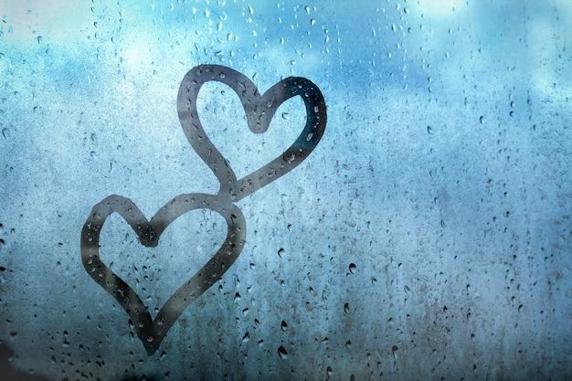 빗방울이 있는 안개가 자욱한 유리창에 손가락으로 그린 두 개의 하트
