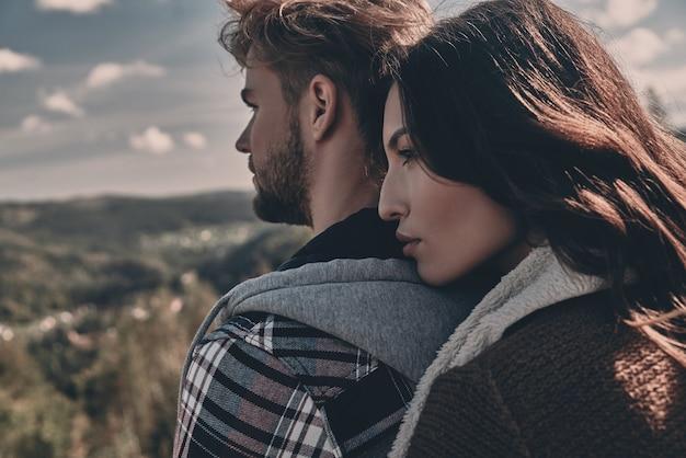 사랑이 가득한 두 마음. 야외에 서 있는 동안 껴안고 멀리 바라보는 아름다운 젊은 부부