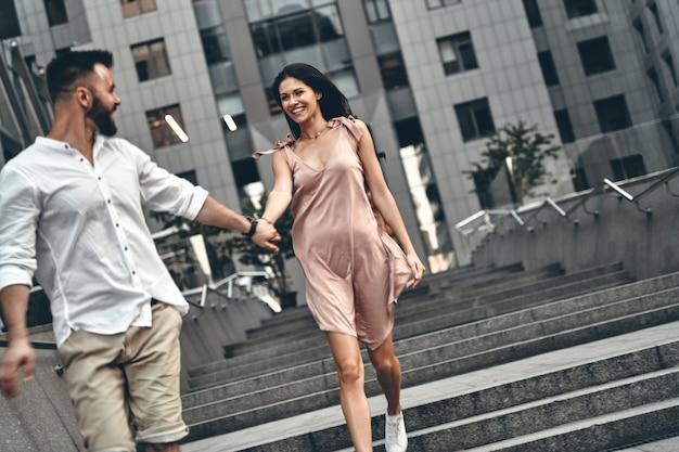 사랑이 가득한 두 마음. 야외에서 계단을 내려가면서 손을 잡고 웃고 있는 아름다운 젊은 부부