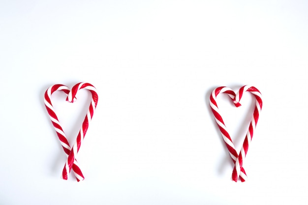 Two hearts made of christmas candy. white and red candy canes in the shape of two hearts on a white background