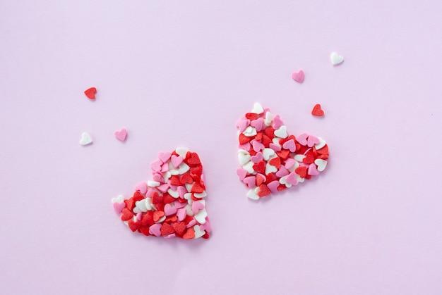 Два сердечка из маленьких красных, белых и розовых сахарных сердечек
