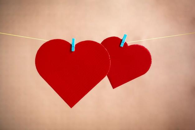 Два сердца из картона и покрашенные красным цветом лежат на веревке с зажимами. концепция дня святого валентина. место для текста.