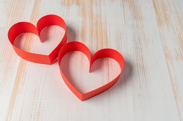 Два сердца из ленты на деревянных фоне.