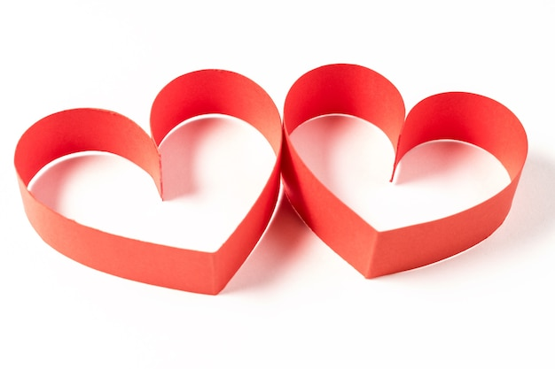 Two hearts made of ribbon on white background.