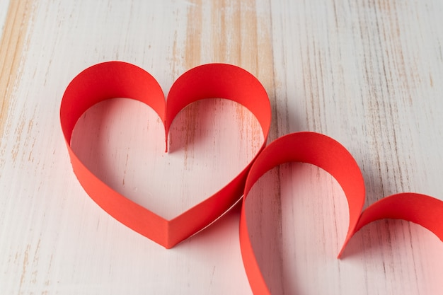 Two hearts made of ribbon on wooden background.
