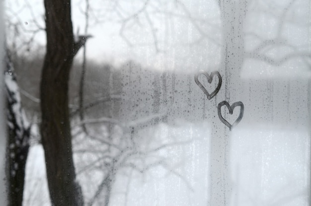 Two hearts painted on a misted glass in the winter