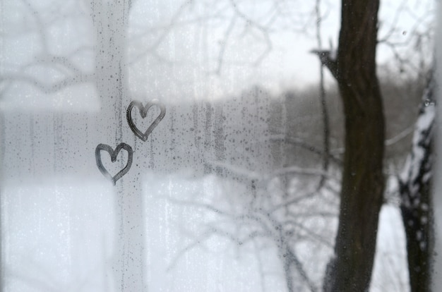 Two hearts painted on a misted glass in winter