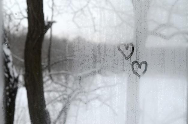 겨울에 안개가 낀 유리에 그려진 두 개의 하트
