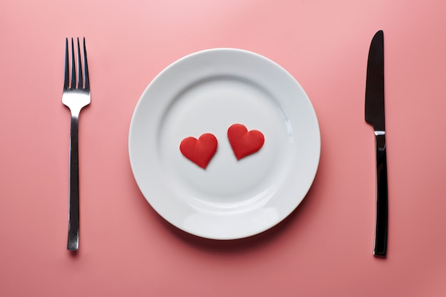 Two hearts in plate with cutlery. romantic dinner in restaurant . meeting of lovers at wedding reception.