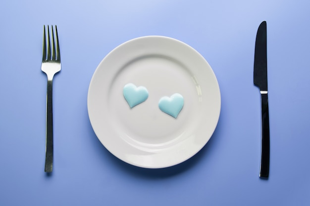 Two hearts in plate with cutlery.