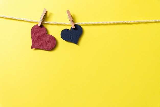 Two hearts on a rope hanging on tiny clothespins on a yellow background.