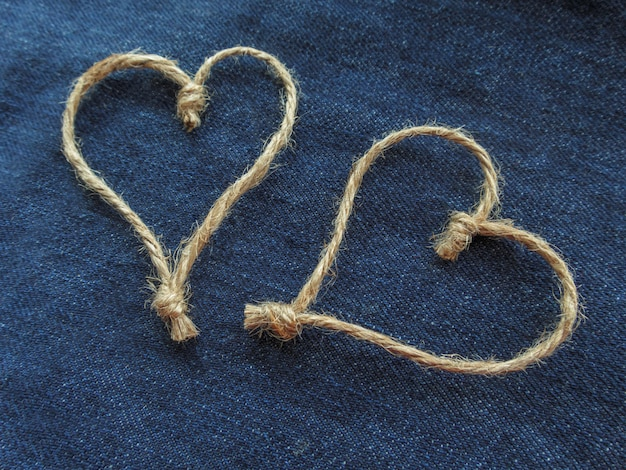 Two hearts sign made of twine on blue denim. world heart day or love concept. close-up