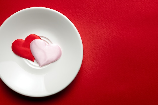 Two hearts at white dish at red background. romance and love concept.