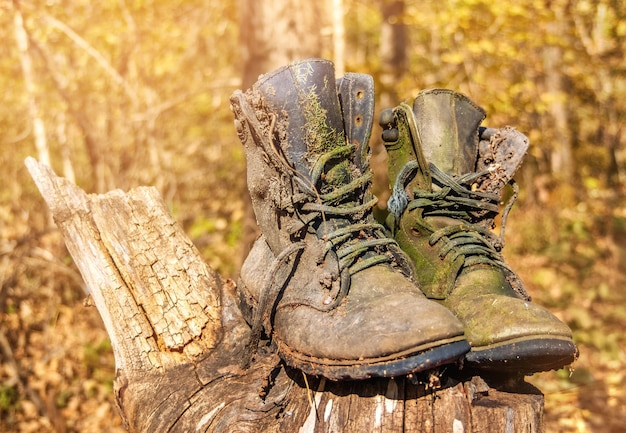 Two heavily worn and old military boots stand against a forest on a sunny day. a pair of abandoned work shoes rot on a stump.
