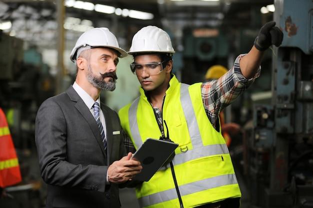 Два инженера тяжелой промышленности стоят на производственном предприятии, используют цифровой планшетный компьютер, обсуждают.