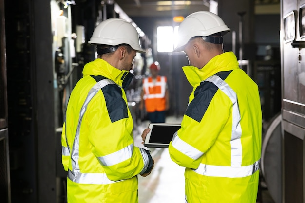 Two heavy industry engineers stand in pipe manufacturing factory use digital tablet computer