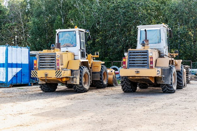 Два тяжелых колесных погрузчика стоят на стройке. оборудование для земляных работ, транспортировки и погрузки сыпучих материалов - земли, песка, щебня.