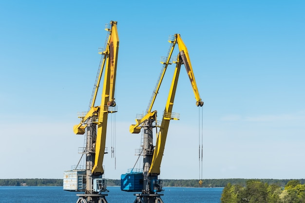 Two high sea cranes for loading containers of cargo on ships and trains.