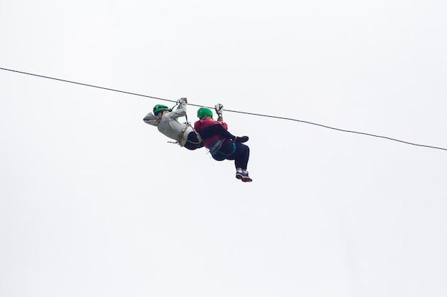 コスタリカの空を背景にジップラインアドベンチャーでハイカー2人