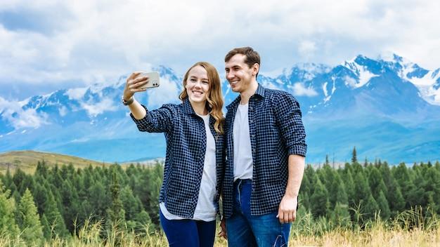 같은 옷을 입은 두 명의 등산객, 한 남자와 한 여자가 산에서 셀카를 찍습니다. 여행 및 휴가 개념.