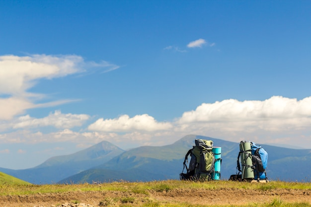 Two hikers backpacks on a grass with mountain peaks in view. carpathian mountains, ukraine