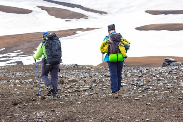 두 명의 등산객이 아이슬란드 산의 하이킹 코스를 따라 걷고 있습니다. landmannalaugar