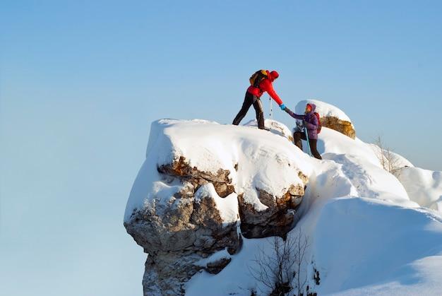 겨울에 산 꼭대기에서 두 명의 등산객이 한 남자가 여성이 깎아지른 듯한 돌을 오르는 것을 돕습니다.