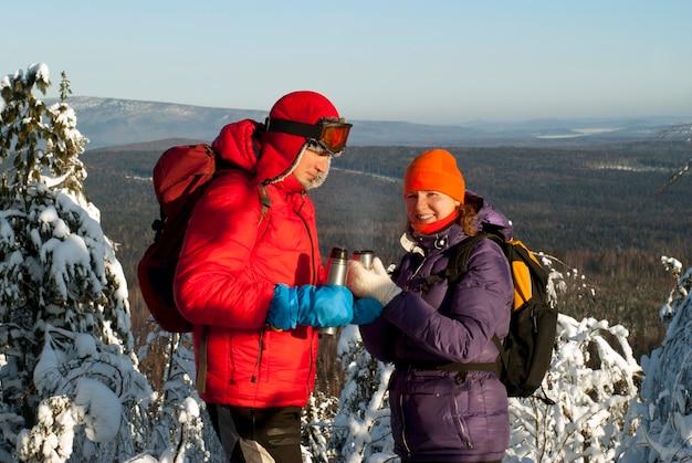 두 등산객은 겨울에 산 꼭대기에 서서 보온병에서 뜨거운 차를 마신다
