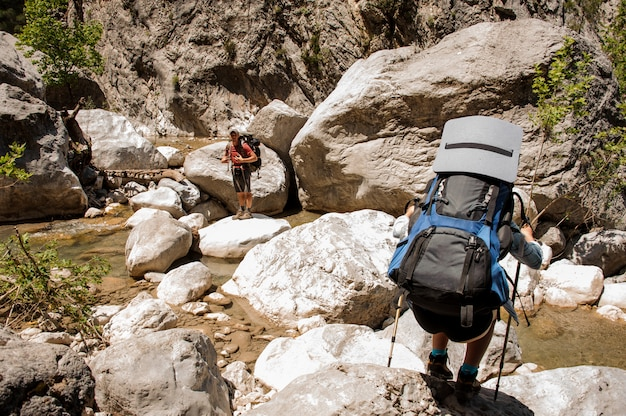 Two hikers travelling through canyon with backpacks
