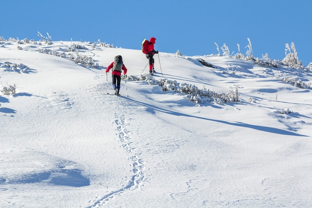 Two hikers with backpacks ascending snowy mountain slope