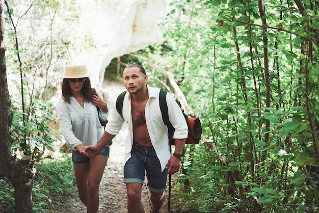 Two hikers with backpacks on the back in nature. man and woman holding hands while walk on a summer day