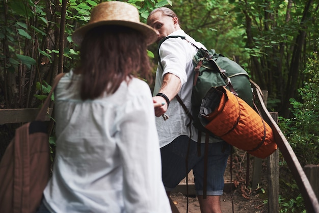Two hikers with backpacks on the back in nature.