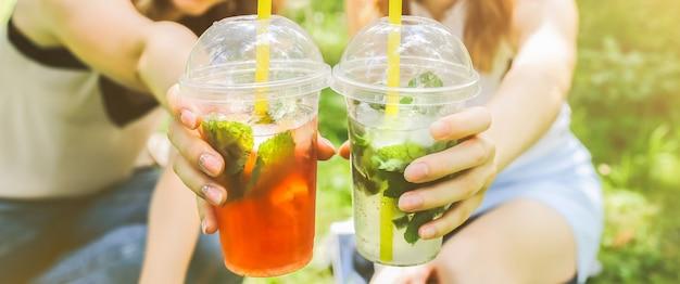 Две хипстерские девушки смеются и пьют летние коктейли на открытом воздухе в зеленой траве. холодные безалкогольные напитки со льдом на вынос. мохито и клубничный лимонад. счастливый образ жизни для отпуска.