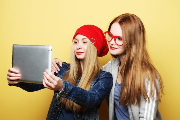 Две подруги-хипстеры, делающие селфи с цифровым планшетом на желтом