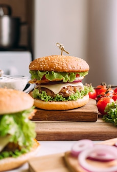 Two home made fresh tasty burgers with lettuce and cheese. ingredients on the table. light food background.