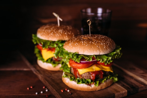 Two home made fresh tasty burgers with lettuce and cheese on wooden rustic table. french fries, tomatoes and sauce. dark food background.