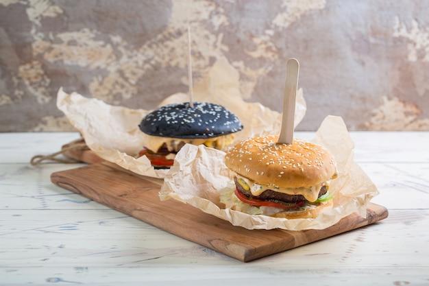 ダークとライトのパン、グリーン、赤玉ねぎ、トマト、キュウリのピクルス、木製のまな板の羊皮紙にチーズを添えた自家製ビーフバーガー2つ