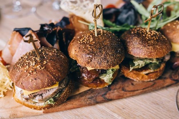 Два домашних гамбургера из говядины с яйцом на деревянном столе.