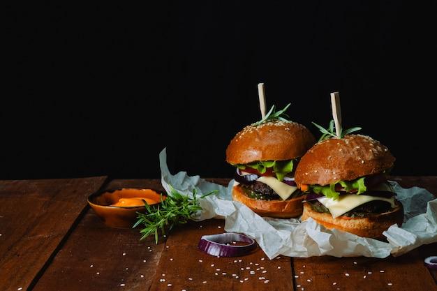 木製のテーブルに醤油と2つの自家製ハンバーガー