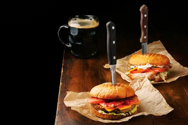 큰 쇠고기, 치즈, 토마토와 나무 테이블과 블랙 테이블에 어두운 맥주 머그잔 두 수제 맛있는 햄버거.