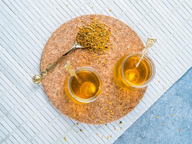 Due vasi di miele con cucchiaio e polline d'api su sottobicchiere di sughero