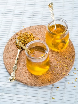 Two honey pots with bee pollen on circular cork coaster over placemat