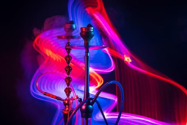 黒の背景に青赤のネオンライトと煙の煙とシーシャ炭と2つの水ギセルボウル