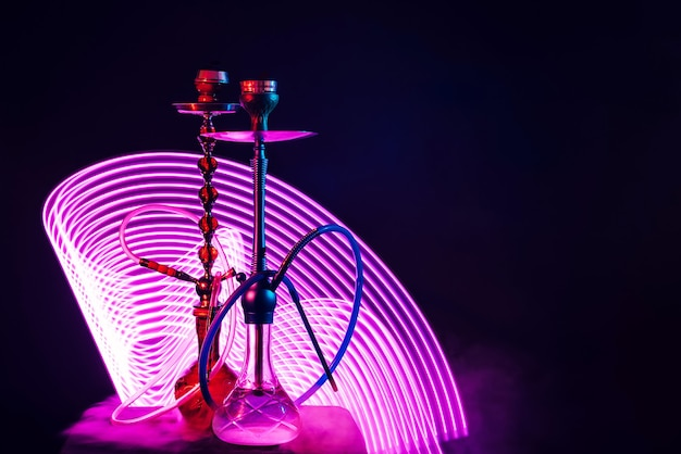 Two hookahs with pipes and bowls and a flask of water with purple neon lighting on a black background